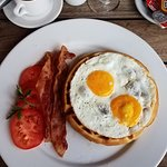 Caffè macchiato and Farmers breakfast. Waffle with eggs, bacon and tomatoes.