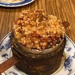 Steamed rice served in a small bamboo basket with chewy pork intestines,