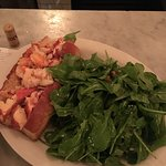 Hot, buttered lobster roll with a lightly dressed green salad.