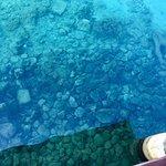Air laut masih jernih. Dasar laut terlihat jelas.