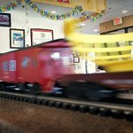 O-scale trains dont come whooshing by, but do deliver the grub, set on table by waitress