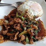 Stir-fried pork with basil + fried egg topped on steamed rice.
