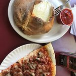 Cheese calzone with a side of sauce and mushroom/bacon pizza