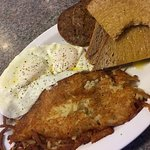 Two fried eggs, sausage patties, wheat toast, and hash browns.