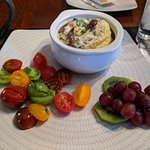 An egg souffle with veggies, pamesn cheese and mushrooms. Served with cooked tomatoes and fruit.
