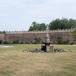 Little castle walled fountain garden during a long hot summer