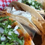 Taco combo (pork, chicken, steak; pork in foreground) for $12 with a large serving of tortilla c