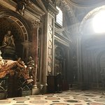 Sunlight shooting through windows of St Peter's and the Statue of Veronica with the veil.