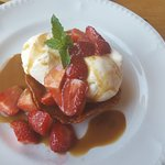 Brandy snap basket with ice cream strawberries and a caramel sauce