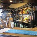 Main bar inside; road outside through window, main entrance door to LHS.