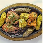 A delicious assortment of Tandoori dishes, sizzling on an iron plate.