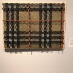 Textile art...yes those are working class screws repurposed to undermine The Burberry plaid