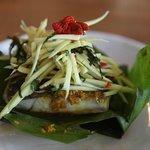marinated sea bass in banana leaf, green mango salad