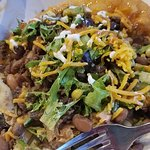 Tradish ground bison Indian Taco with honey drizzled over the edges of the fry bread