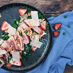 Grilled Tuna resting on a fresh salad pillow with strawberries, roasted almonds and parmesan.