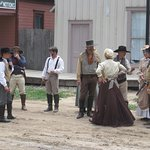 Characters gather for pictures after the gunfight.
