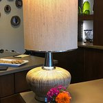 Lamp on check-in desk with fresh flowers.