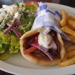 Gyro sandwich plate with fries and greek salad.