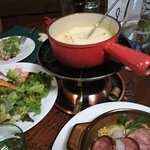 Delicious fondue wih some salad and local charcuterie dishes