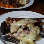 oatcake with bacon, potatoes and black pudding with melted cheese very tasty and very filling