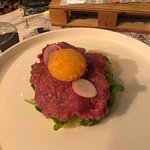 Beef tartare bread salad with tomatoes and fired egg