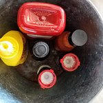 Condiments and crayons in a bucket on the table. Lots of crayons. No fight for the green one.