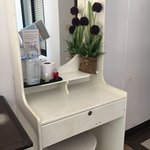 Low quality furniture with chipped paint and dirty/dusty fake flowers