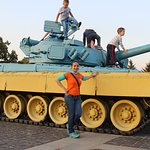 a patriotic tank infront of the life-sezed statue, in national flag color