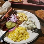 Some of the sides are pinto beans, mac and cheese, potato salad, and corn