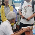 Young Vietnamese interacting with older citizen inside Central Post Office.