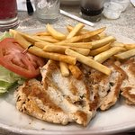 Grilled chicken breast, lettuce, tomato, and fries.