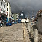 Along The Barbican, threatening sky over tall ship, open top bus and best pubs