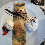Crèpe with slices banana and chocolate saus inside, aside vanilla ice and cream.