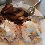 eggs benedict on biscuits with potatoes and gravy