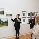 A curator lectures on a photo series during a 'Meet the Curator' event.