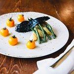 Filetto di merluzzo laccato al nero di seppia con fagiolini e pomodorini confit