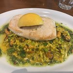 One of our signature dishes - fillet of fresh fish with saffron, pea and smoked salmon risotto.