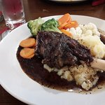 The lamb shank which comes on a bed of mash potato with fresh vegetables and mint gravy.