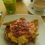 Freshly scrambled eggs on wholemeal toast with bacon strips.