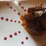 Pierna de cordero lechal al horno rellena de ciruela pasa, con falsa salsa de Romescu