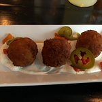 Charred Corn Croquettes with Roasted red pepper, lime crema, cilantro, pickled jalapeno