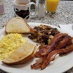 Scrambled eggs, bacon, home fries, Rye toast, coffee, and OJ.
