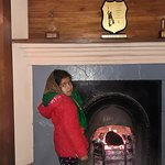 My daughter beside fireplace.