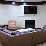 Sectional sofa surrounding TV and fireplace in the hallway near elevators