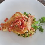 Pan seared cod served on a bed of quinoa tabbouleh, topped with a tomato-mint salsa