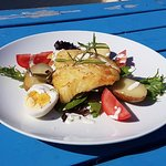 Pan seared cod, served atop of fingerling potatoes, tomato & greens, with savory buttermilk dres