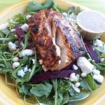 Arugula and beet salad topped with wild salmon.