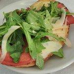 Bruschetta de rúcula, bresaola (carne curada) y grana (queso)