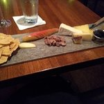 Cheese board with gluten-free crackers, sliced apple, glazed pecans, berries, cheese, and honeyc