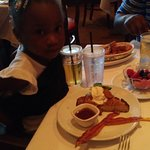 My granddaughter with her pancake, fruit and bacon